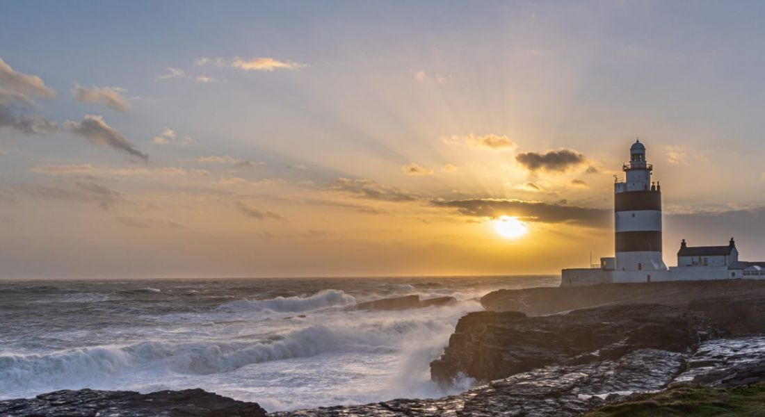 A photo of Hook Lighthouse in Co Wexford on the south-east coast of Ireland as the sun is setting.