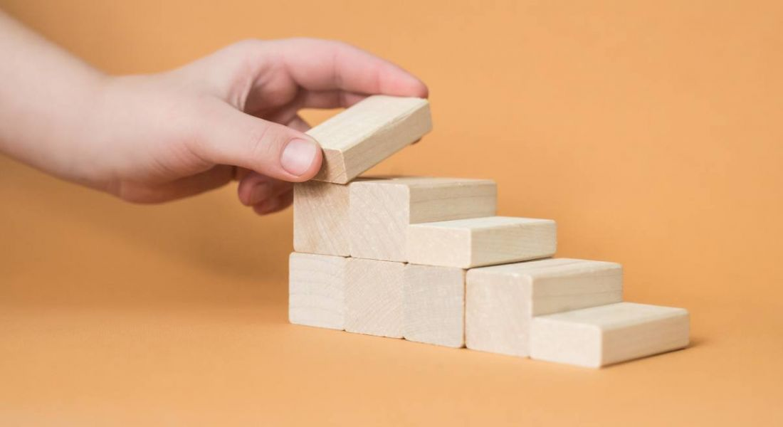 Hand arranging wooden blocks into a stepped shape against a pale orange background.