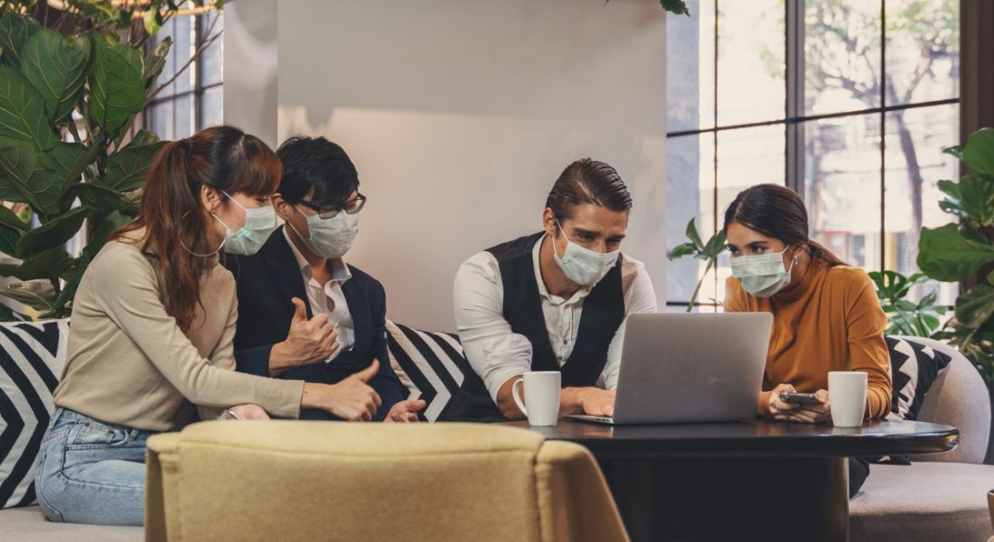 A group of colleagues are wearing face masks at work in a casual office space.