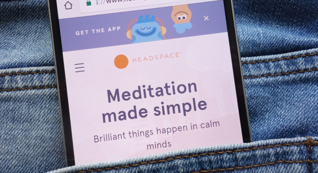 A mobile phone in a jeans pocket open on the Headspace homepage.