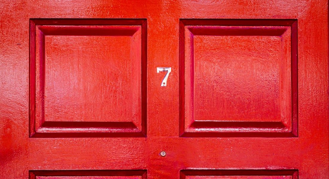 A gold number seven on a red front door.