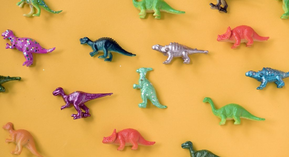 Colourful toy dinosaurs are laying against a light orange background.
