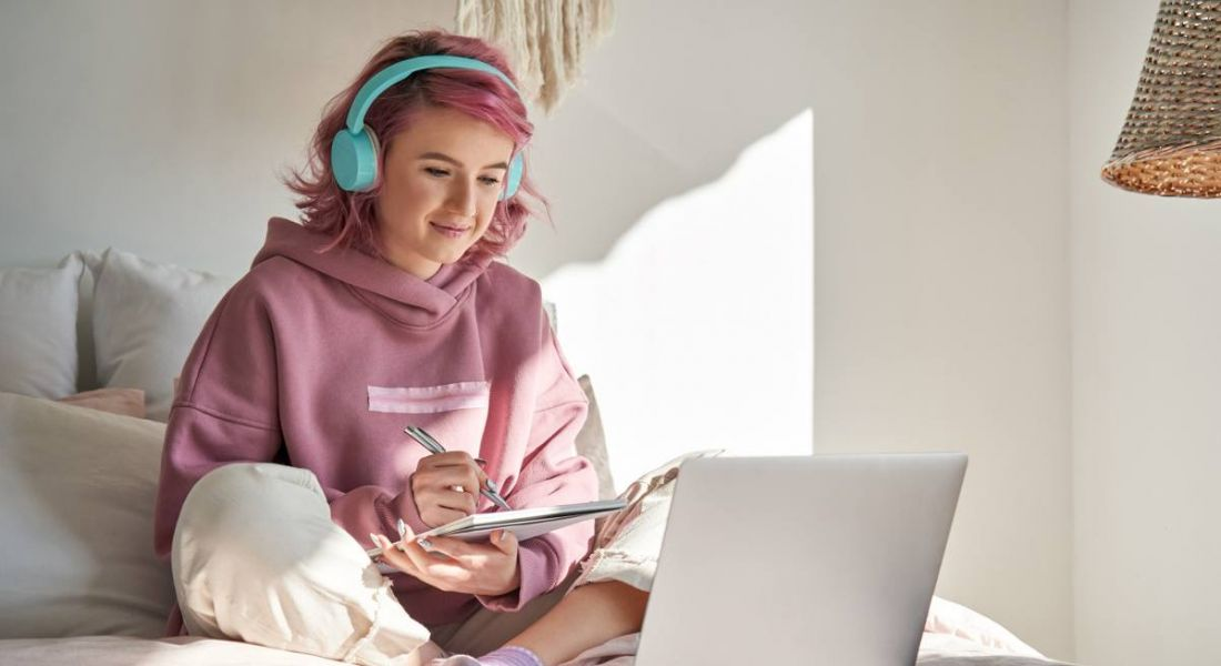 A young student in a pink hoodie is sitting on her bed attending a virtual lesson on her laptop.