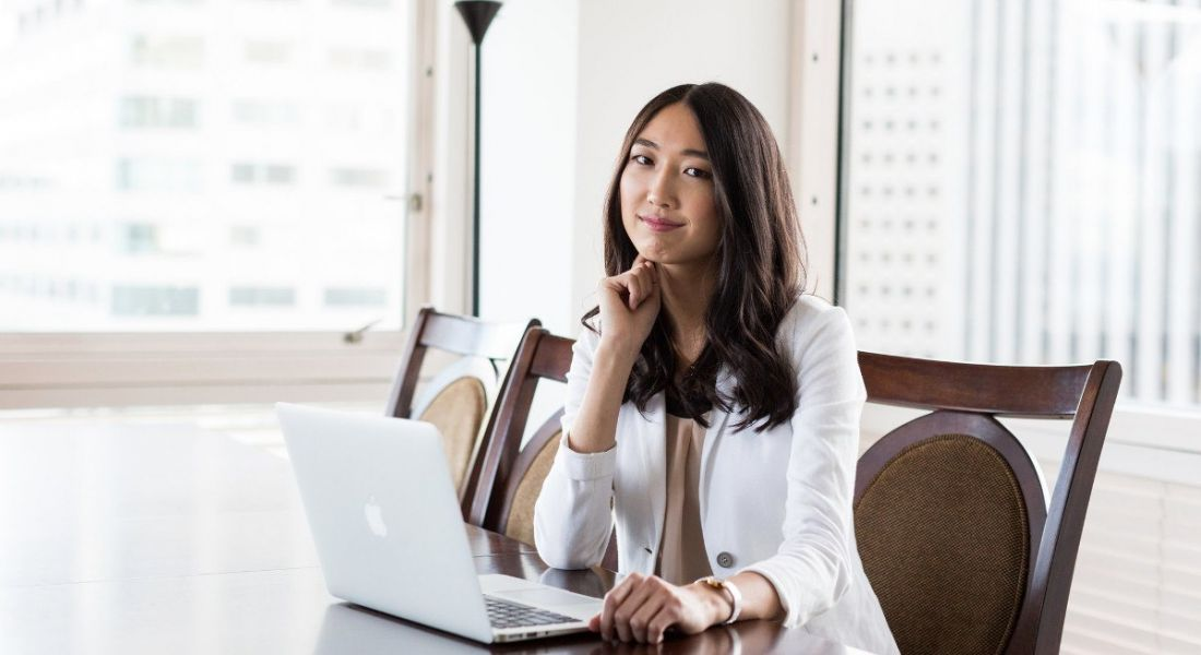 Jessica Mah of InDinero is sitting in a brightly lit office smiling into the camera.