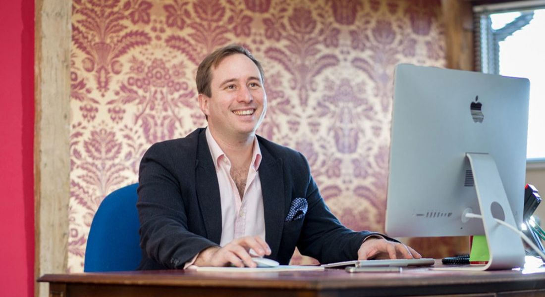 Patrick Tame is sitting at a computer in an office with patterned wallpaper in the background.
