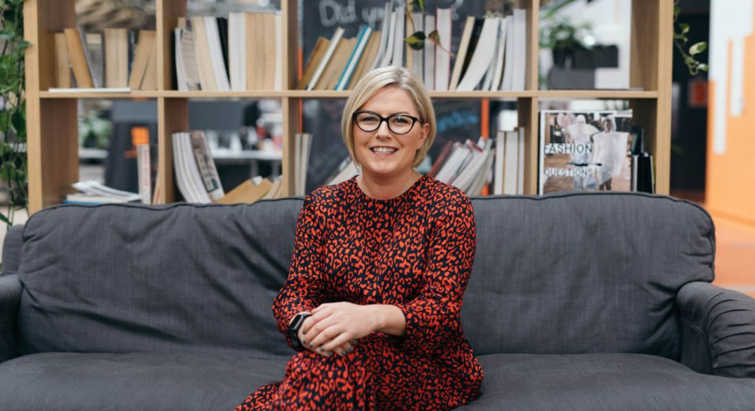 Sarah Bourne of Zalando is sitting on a grey couch in front of bookshelves and smiling into the camera.