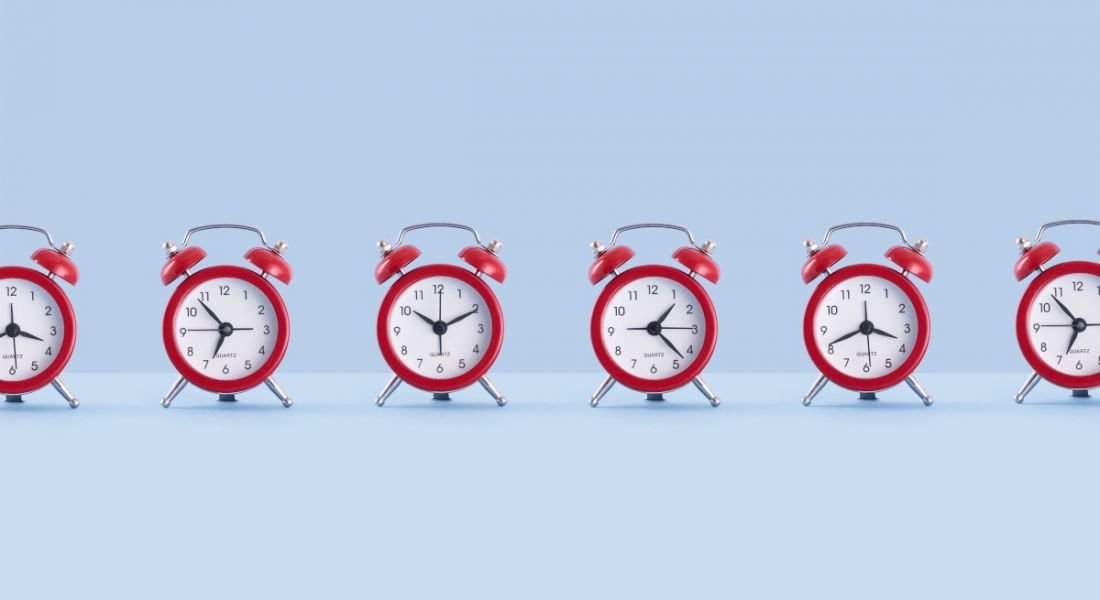 A line of small red alarm clocks against a blue background, all showing different times.
