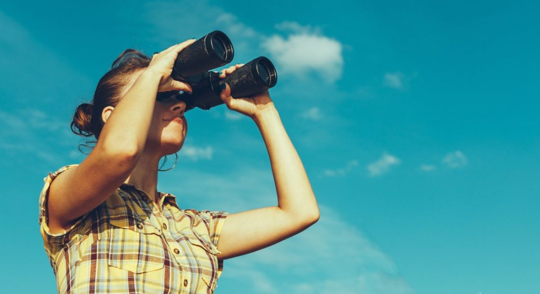A woman in a check shirt looking through binoculars against a blue sky with fluffy white clouds.