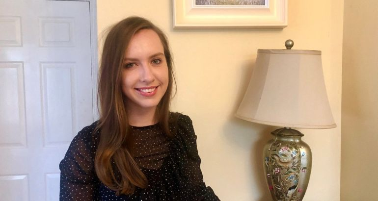 Laura Sinnott, a data scientist at Aon, is standing in a living room and smiling into the camera.