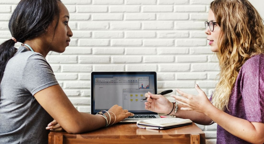 Two women are discussing something at a table in a brightly lit workspace.