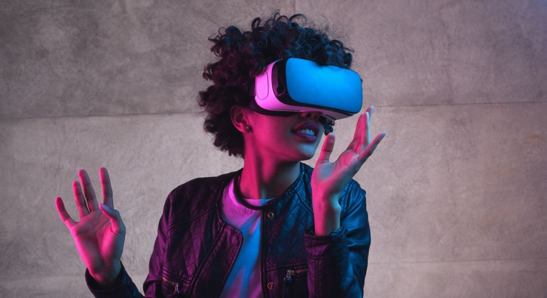 A woman is lit up by pink lighting and wearing a virtual-reality headset.