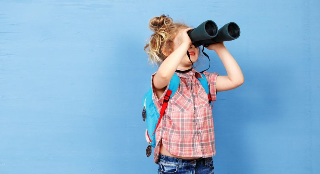 A young girl is looking through binoculars against a blue background, symbolising a job hunt.