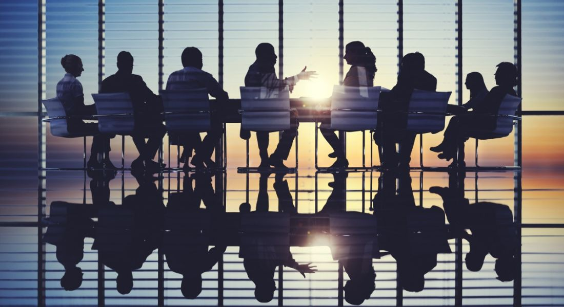 Silhouettes of board members meeting in a room at sunset.
