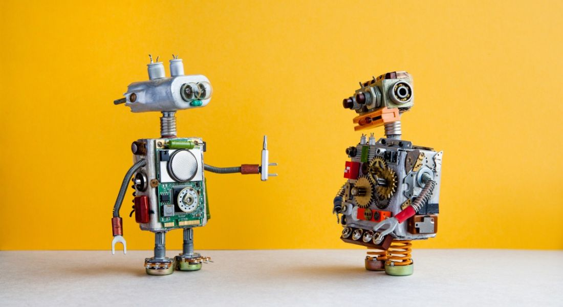 Two toy robots are talking to each other against a yellow background.