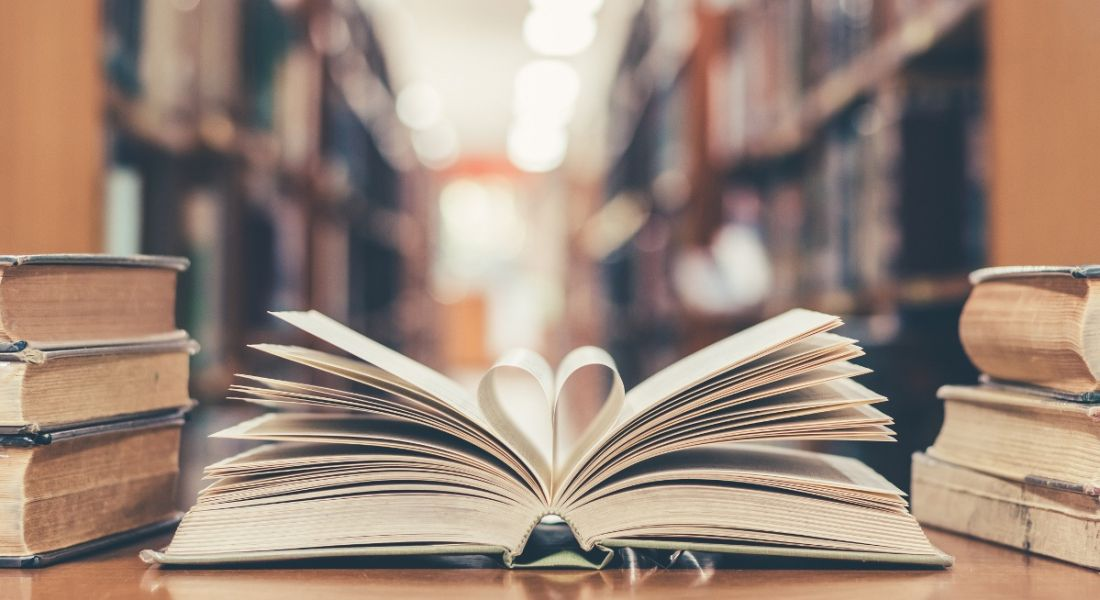 Book on a table in a library, with two pages forming the shape of a heart.