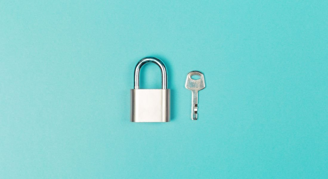 A small silver padlock and key sit against a blue background.