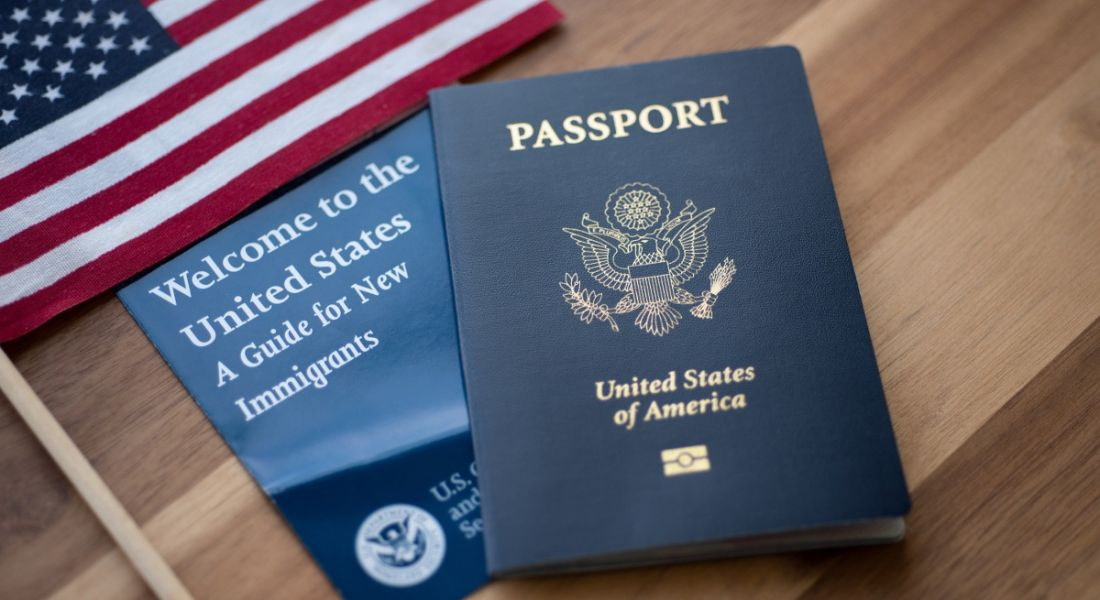 US passport next to a guide for people relocating to the country and the US flag on a wooden table.