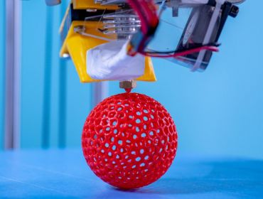 3D printing a red sphere in industrial lab against a blue background.