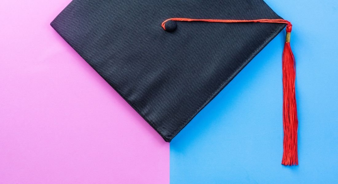 Graduate cap on a pink and blue background.