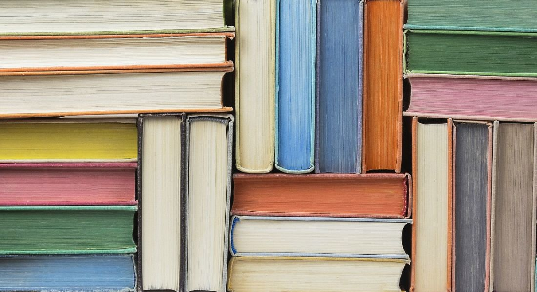 Stacks of books in different colours, symbolising lifelong learning.