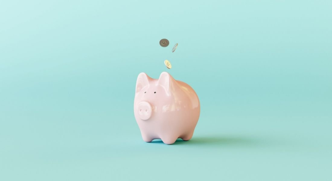 Pink piggy bank against a turquoise background.