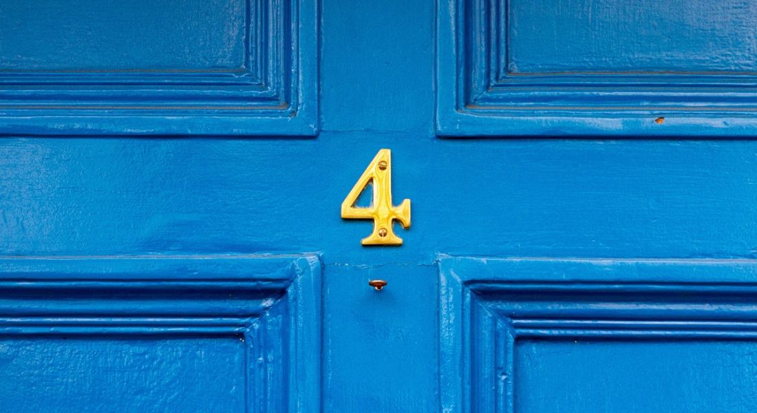 Gold number four on a bright blue front door.