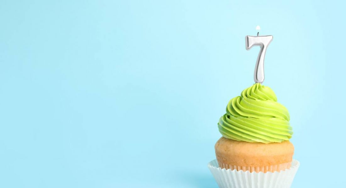 Birthday cupcake with number seven candle on blue background.