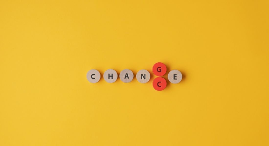 The word 'change' is spelled out on small wooden circles that are placed against a yellow background. The circle for the letter G is coloured in red and is being replaced by another circle that features the letter C, effectively switching 'change' to 'chance'.