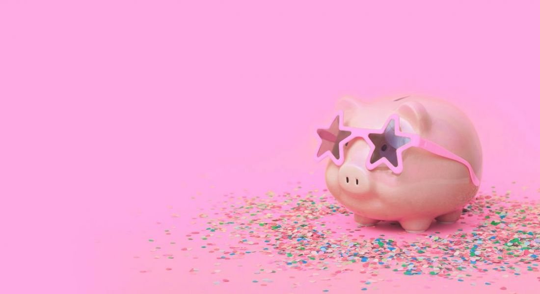 Pink piggy bank with confetti and star-shaped sunglasses on a pink background, symbolising financial wellbeing.