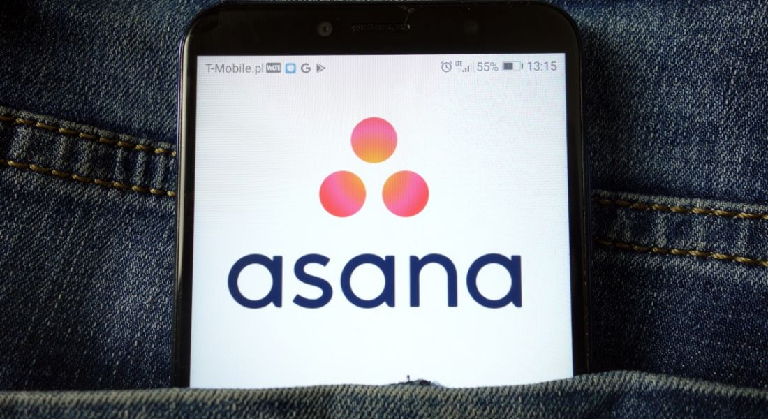 The Asana app logo is displayed on a mobile phone, which is stick out of a person's trouser pocket. The logo includes the name of the company and three pink dots.