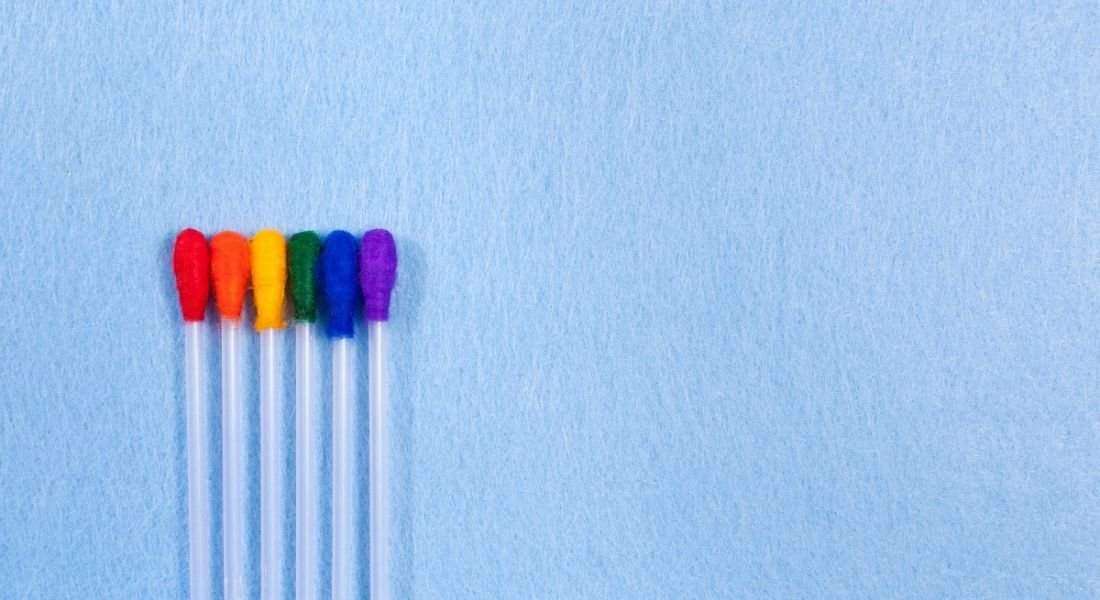 Rainbow-coloured cotton buds against a blue background, symbolising diversity and inclusion.