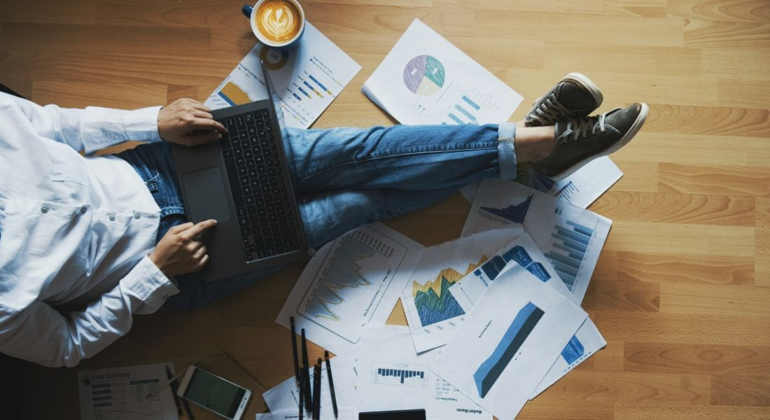 A woman is sitting on a wooden floor surrounded by papers with a laptop while working from home.
