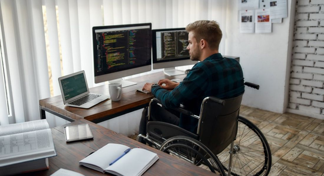 A programmer is sitting at his desk in a wheelchair, working on software development.