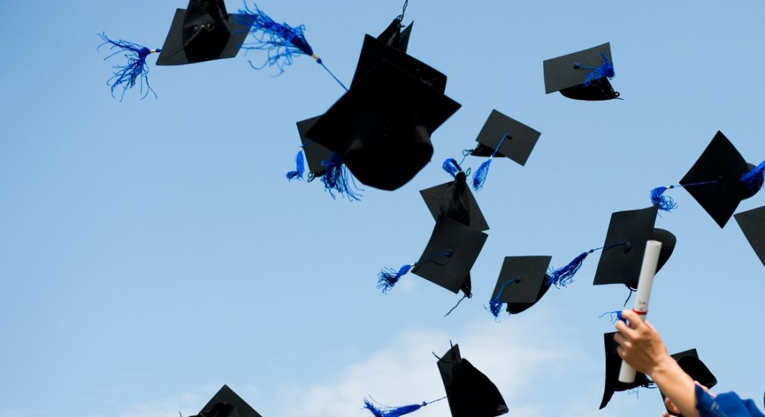 Graduates throwing their hats up in the air against a bright blue sky.