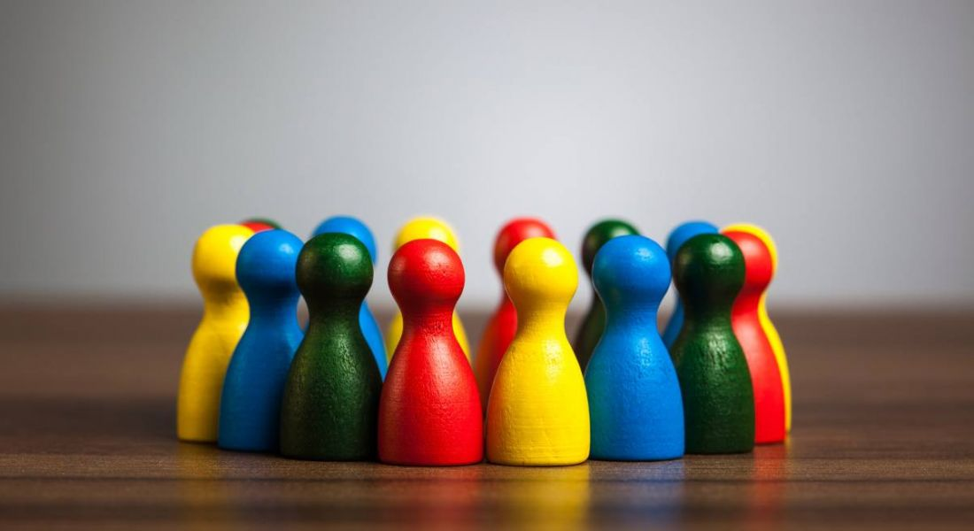 Wooden figures of all different colours huddled together on a wooden desk, representing diversity and inclusion.