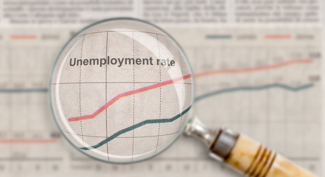 A magnifying glass is looking at unemployment rates on a document.