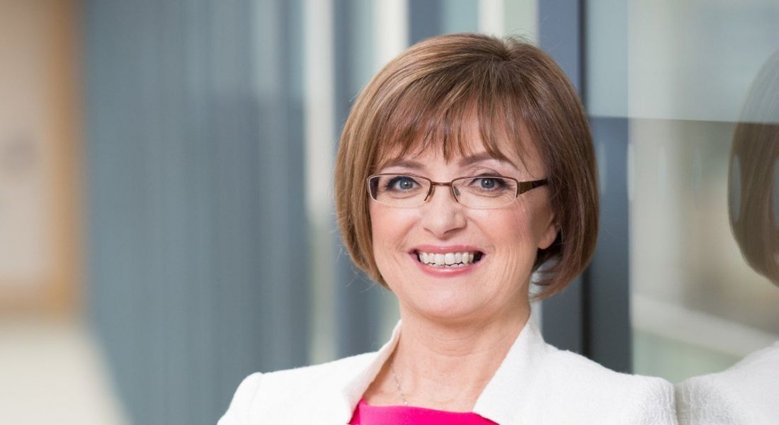 A headshot of Microsoft Ireland's Cathriona Hallahan, a woman with short brown hair and glasses wearing a white blazer and pink top.