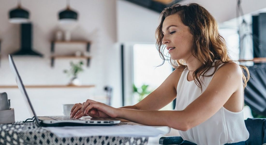 Woman working at a laptop in a casual setting at home.