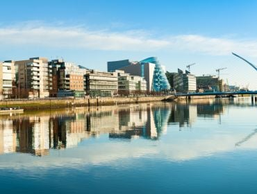 A line of office buildings along the quays in Dublin city centre with the river Liffey in the foreground and the Samuel Beckett bridge in the background.