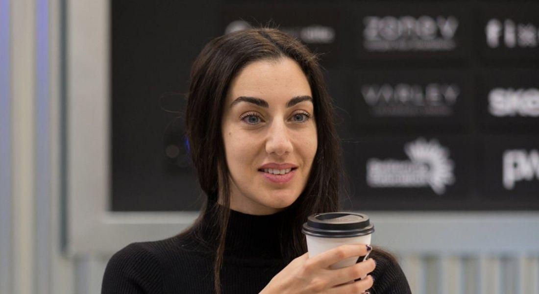 A woman with dark hair wearing a black polo neck jumper, holding a takeaway coffee cup and smiling off camera.