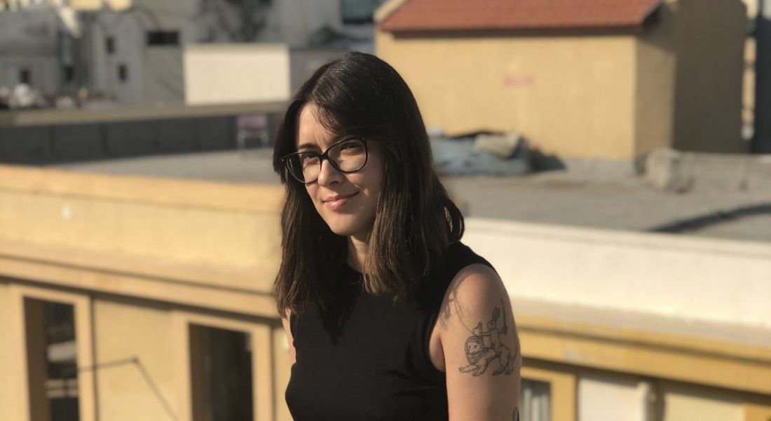 Gaming-app developer Galit Steinberg is sitting on an outdoor rooftop and smiling into the camera.