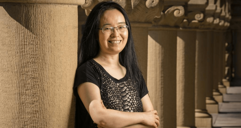 Jessie Jiang of Create and Learn is standing in an old-fashioned building and smiling into the camera with her arms folded.