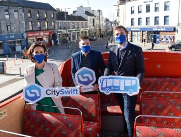 A woman and two men sit on an open-top red bus in Galway city. They're all wearing blue face coverings and holding signs with the CitySwift logo or a picture of a bus.
