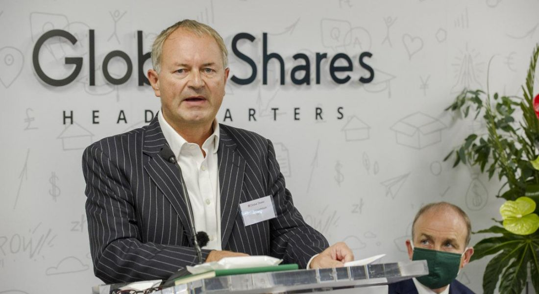 Tim Houstoun stands at a podium in front of a sign that reads 'Global Shares', with Taoiseach Michael Martin sitting in the background.