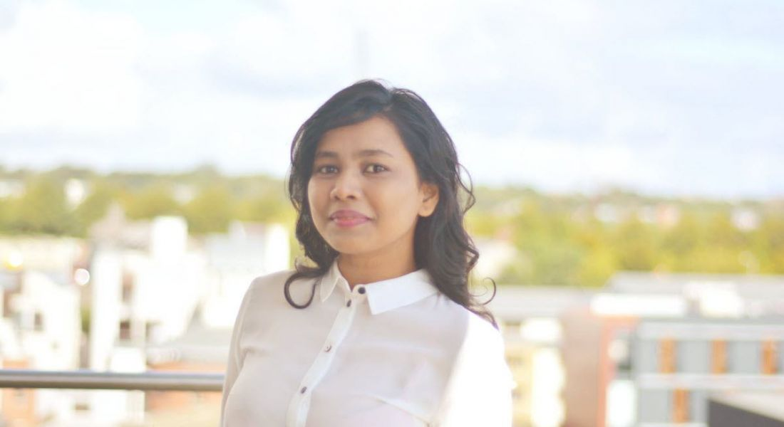 Data analytics graduate Asmita Satpute of Aon is standing on a balcony and smiling into the camera.