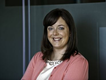 A woman with dark hair wearing a pink blazer and white blouse smiles at the camera against a dark wall. She is Susanne Jeffery from Accenture.