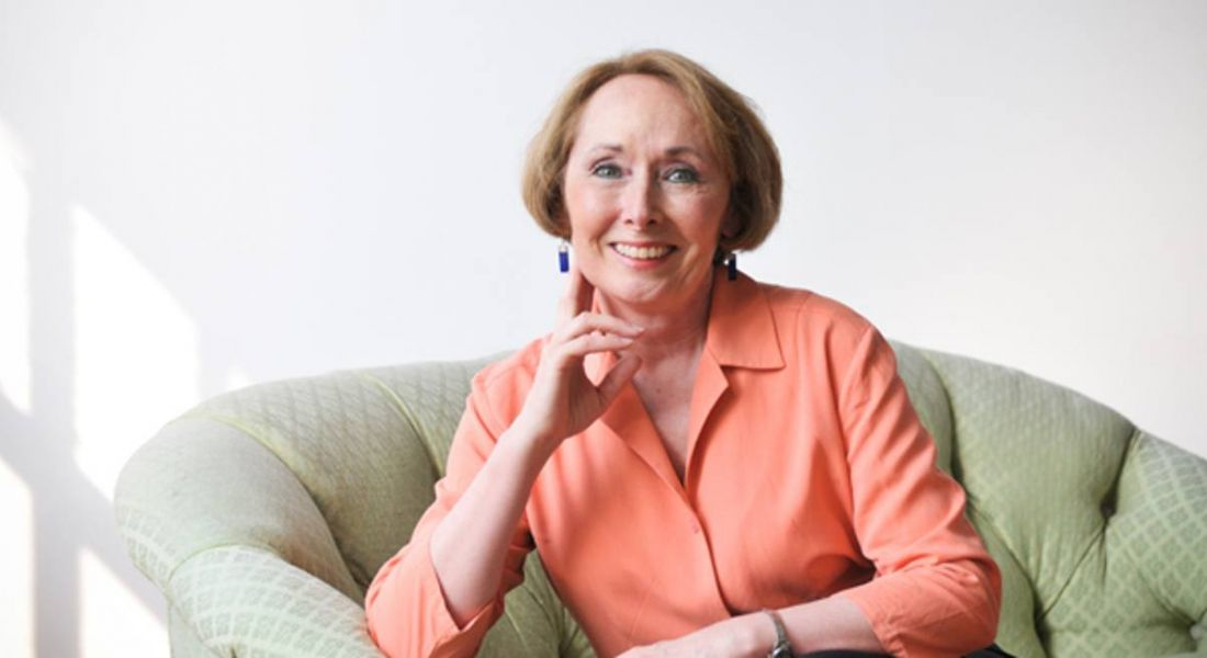 Expert on imposter syndrome Dr Valerie Young is sitting on a green couch in a brightly lit room and smiling into the camera.
