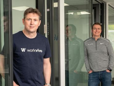Two men in Workvivo shirts stand in a bright office space.