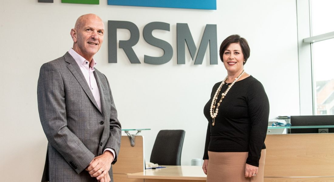 A man and woman are standing beside each other and smiling into the camera in front a wall branded with the RSM logo.