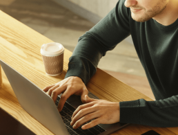 Close-up image of a man working on his laptop at home.